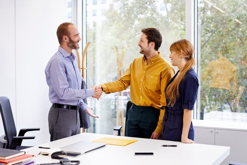 A young couple shaking hands with a tax professional in his office.