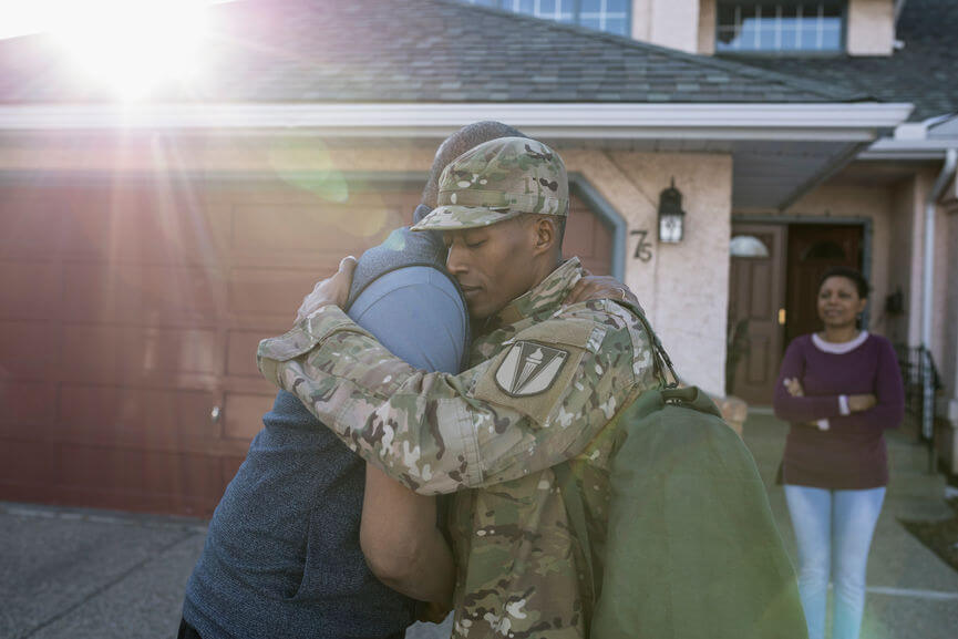 military man hugging his family
