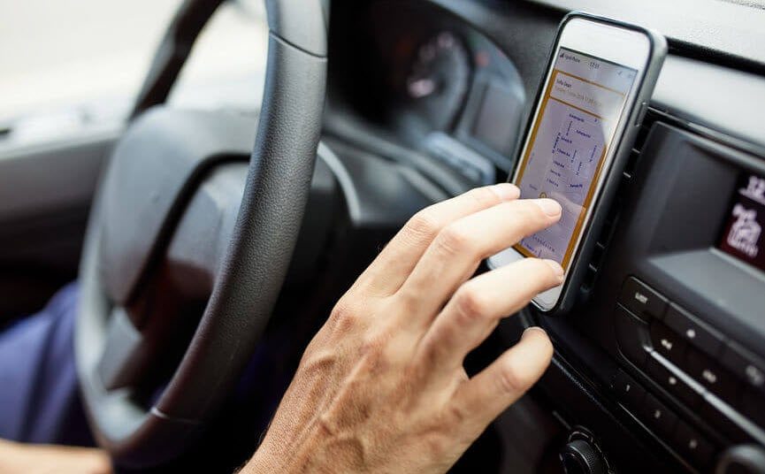 Close-up of driver using a mobile app on his phone