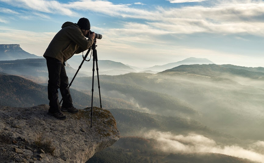 Photographer taking pictures on the edge of a cliff