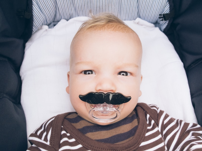 Baby with a pacifier shaped like a mustache.