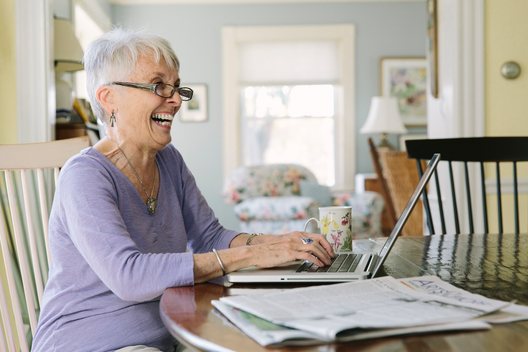 Senior woman on laptop and laughing