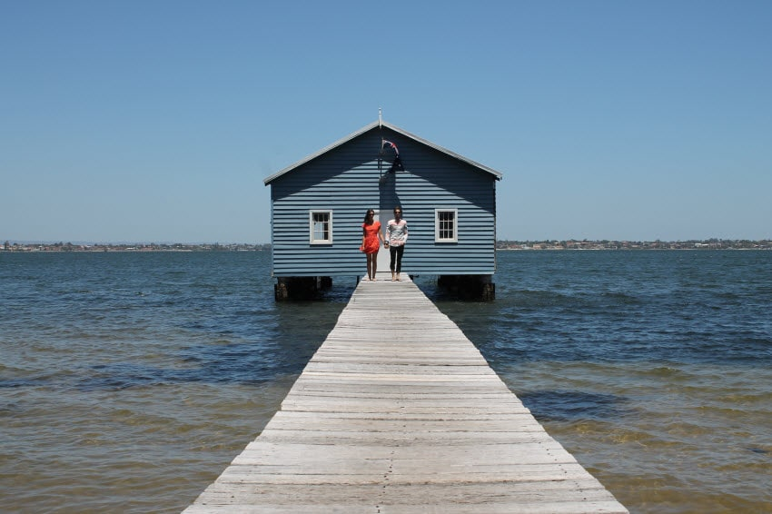 House on the water with a long dock and a couple holding hands in the distance