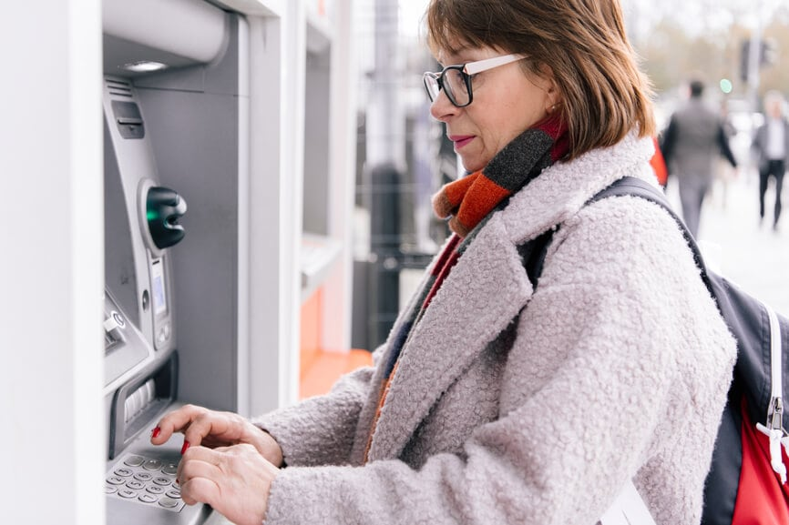 Woman using an ATM to withdraw her tax refund.