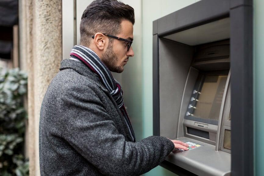 Man checking his account balance at an ATM.