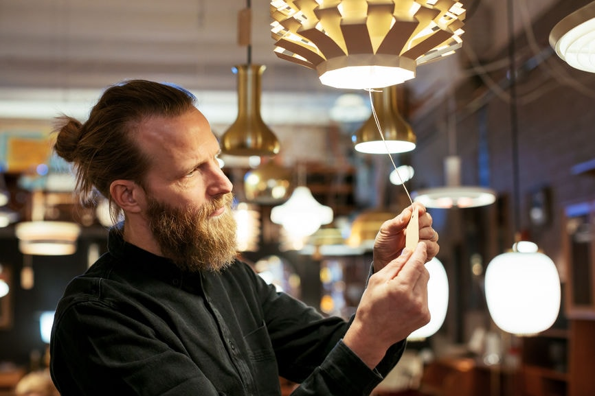 Man looking at price tag on lamp.