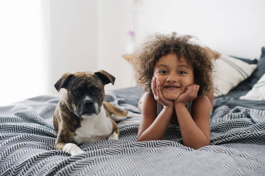 Child smiling in bed with her puppy.
