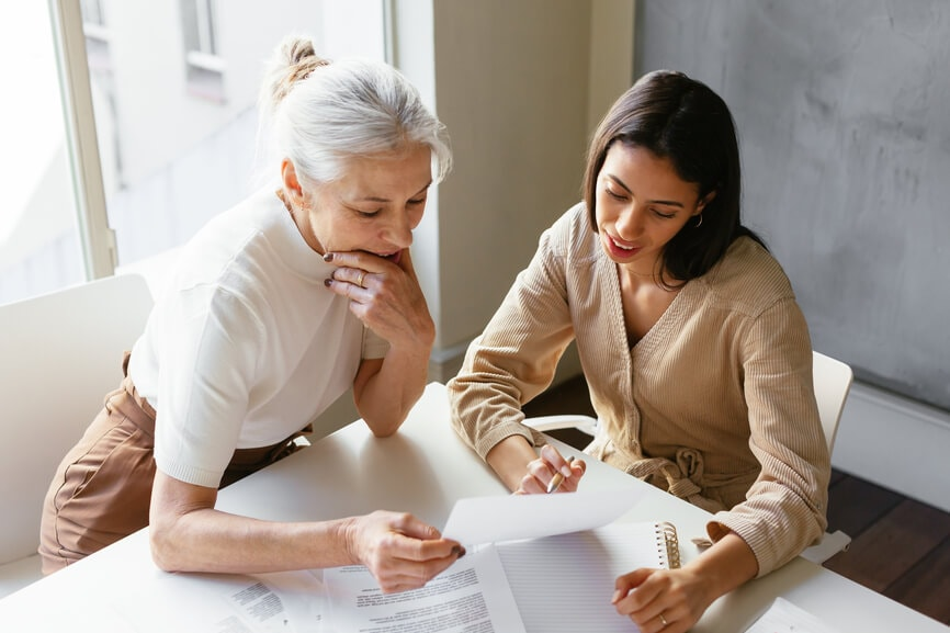 Two business women at a desk looking over paperwork to find out how to lower their taxable income.