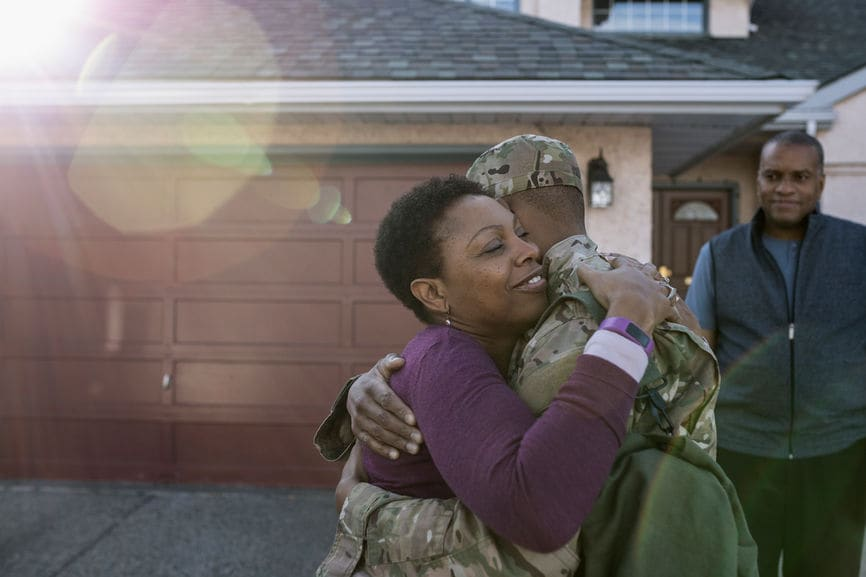 Affectionate soldier son and mother hugging in driveway