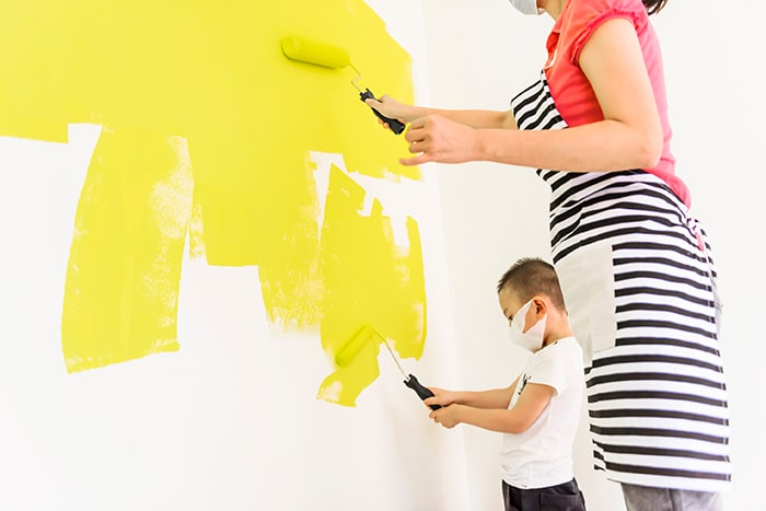 Mother and son painting wall yellow
