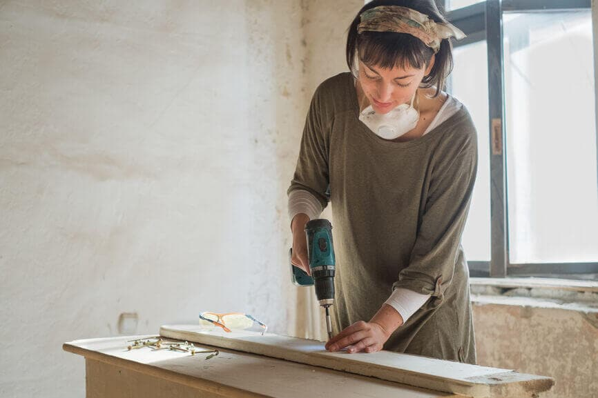 woman using a drill on wood planks renovating her home