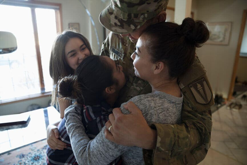 member of the armed services hugging his daughters